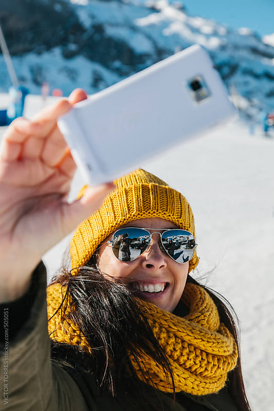Happy Woman Taking a Selfie in the Snow Resort by VICTOR TORRES for Stocksy United