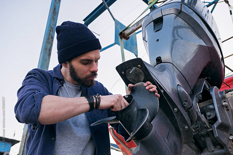 Boat repairman checking motor by Danil Nevsky for Stocksy United