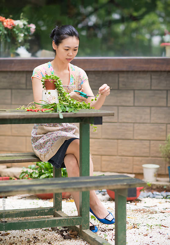 Young woman trimming plants in garden  by Lawren Lu for Stocksy United