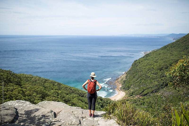 Female Hiker overlooking the ocean by Reece McMillan for Stocksy United
