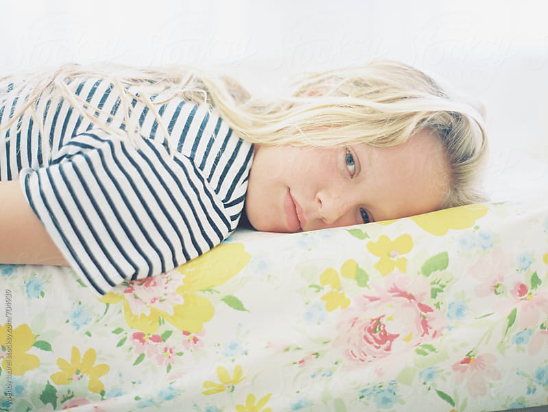 blonde girl tween in striped shirt on vintage floral sheet portrait by wendy laurel for Stocksy United