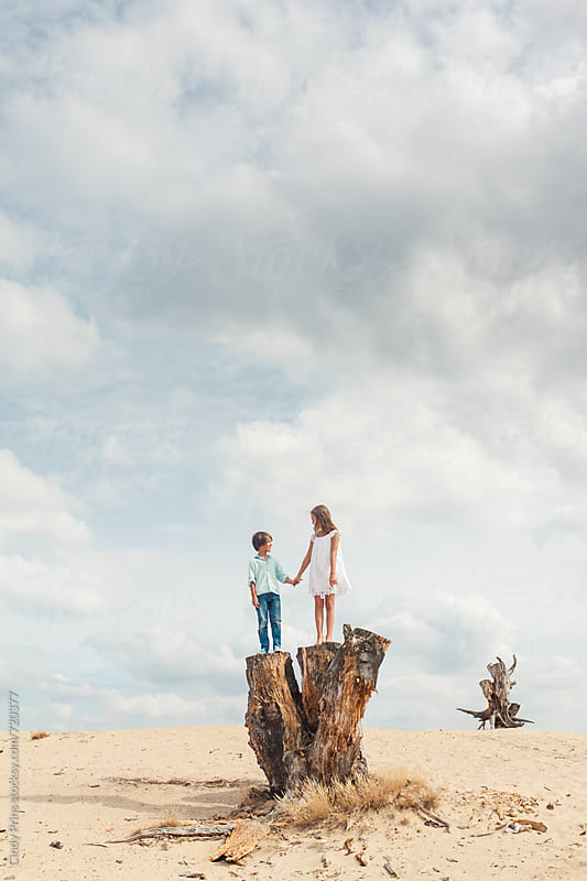 Little boy and girl standing on a tree trunk in the sand underneath a big sky by Cindy Prins for Stocksy United