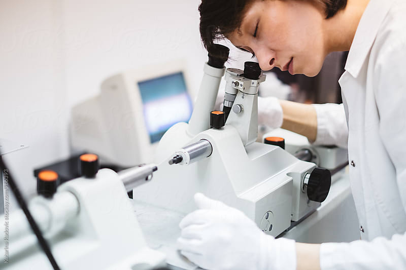 Female Chemist Looking Through the Microscope by Katarina Radovic for Stocksy United