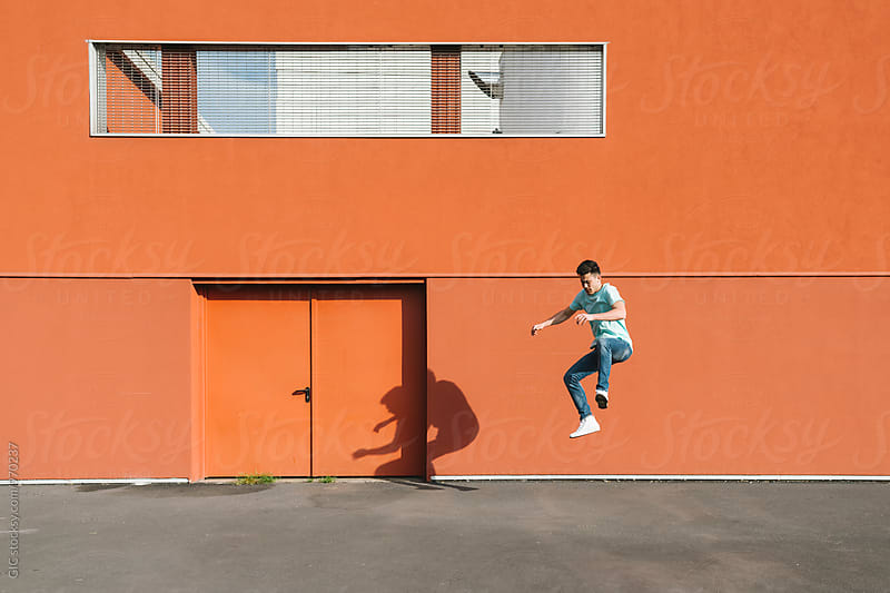 Asian man jumping in urban area by Simone Becchetti for Stocksy United