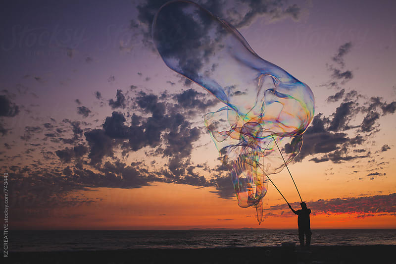 Large bubble floating along the beach at sunset. by Robert Zaleski for Stocksy United