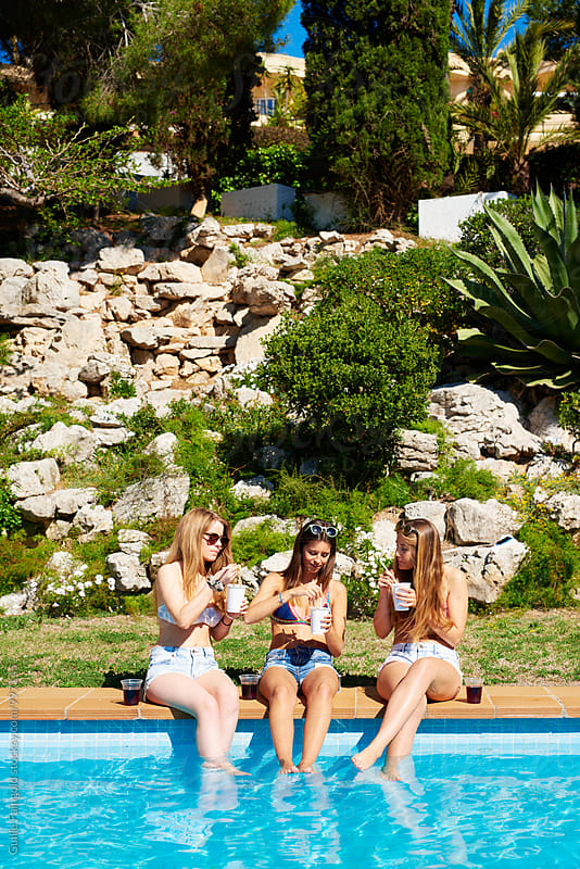 Three girlfriends eating noodles on edge of swimming pool in garden by Guille Faingold for Stocksy United