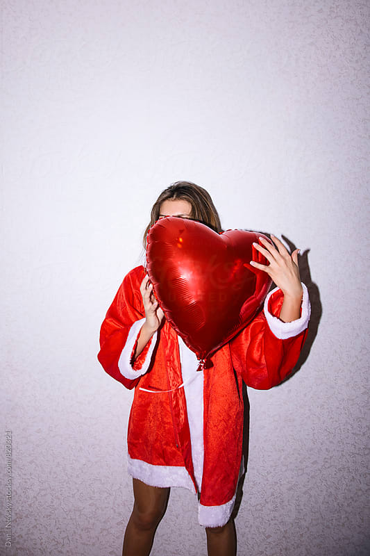 Young woman in Santa Claus costume hiding her face with red balloon by Danil Nevsky for Stocksy United