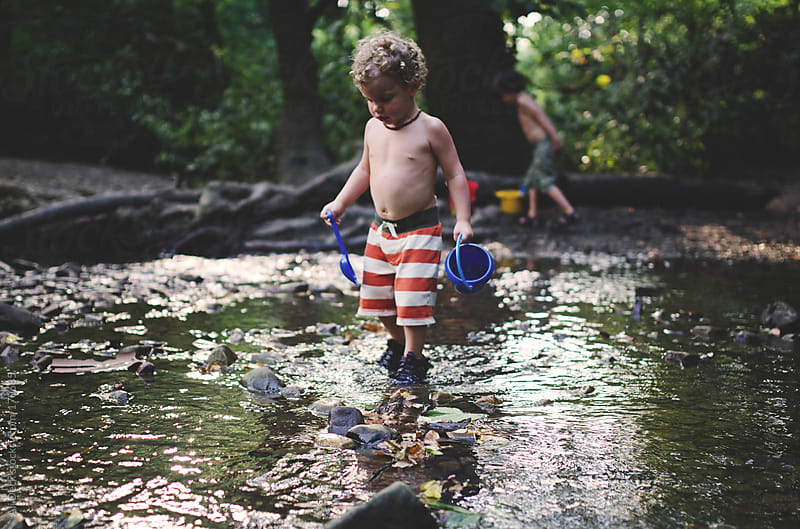 A Young Boy in a Creek by Ali Deck for Stocksy United