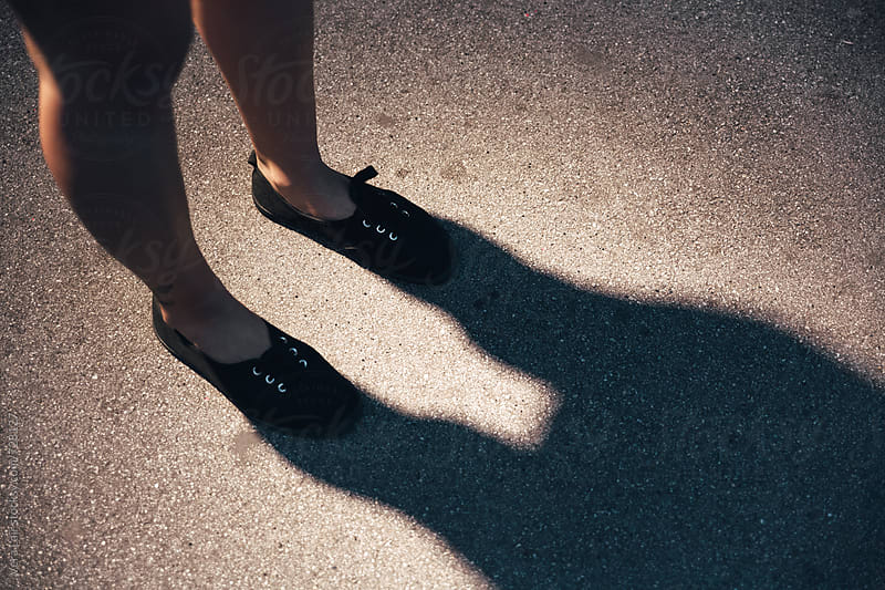 Woman legs in the shadow by Vera Lair for Stocksy United