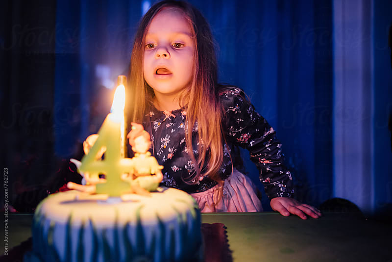 Girls blowing up a candle on her birthday cake by Boris Jovanovic for Stocksy United
