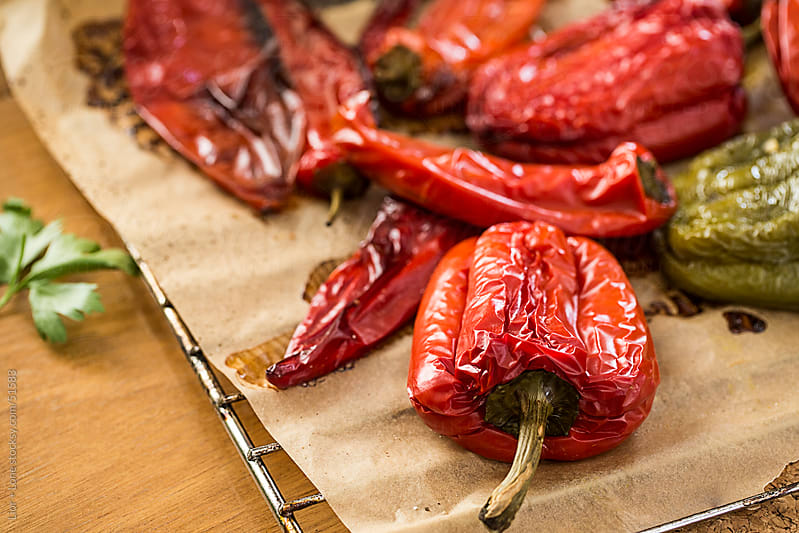 Red and green roasted peppers on baking paper by Lior + Lone for Stocksy United