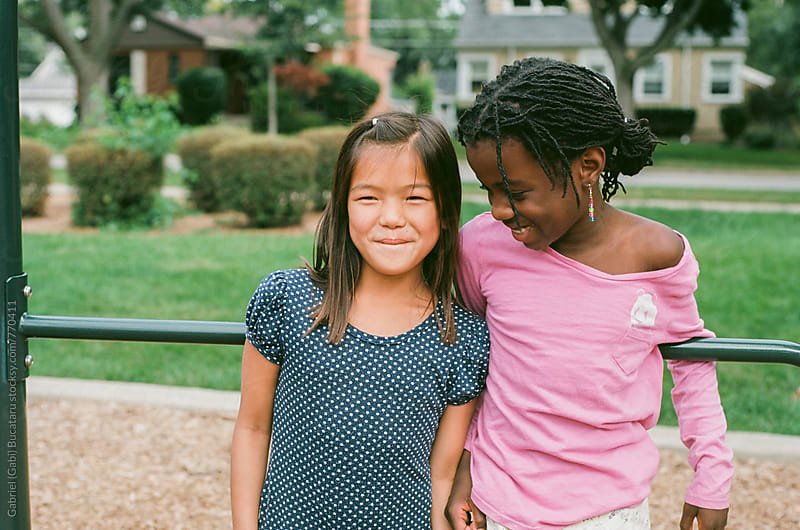 Asian and African American friends on playground by Gabriel (Gabi) Bucataru for Stocksy United