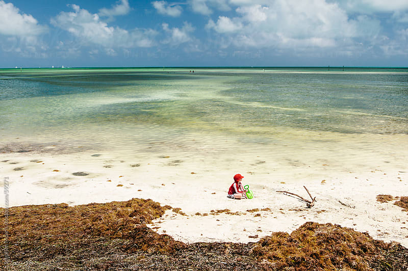 Boy Playing on Tropical Beach by Stephen Morris for Stocksy United