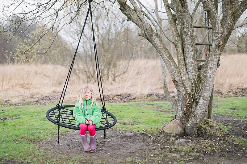 Girl sitting in  a swing by Jonas Räfling for Stocksy United