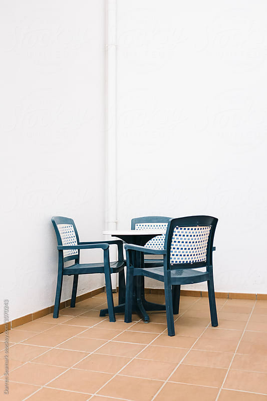 Table and chairs in the a corner of a walled terrace by Darren Seamark for Stocksy United
