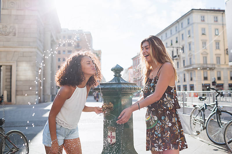 Two girls play with a water at the fountain on a hot day by michela ravasio for Stocksy United