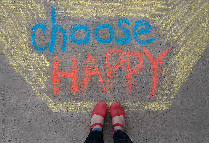 Feet standing above a positive message that says Choose Happy by Carolyn Lagattuta for Stocksy United