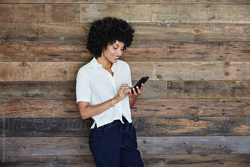Millennial businesswoman looking at phone in office by Trinette Reed for Stocksy United