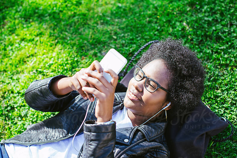 Latin woman lying on the grass using her phone. by BONNINSTUDIO for Stocksy United