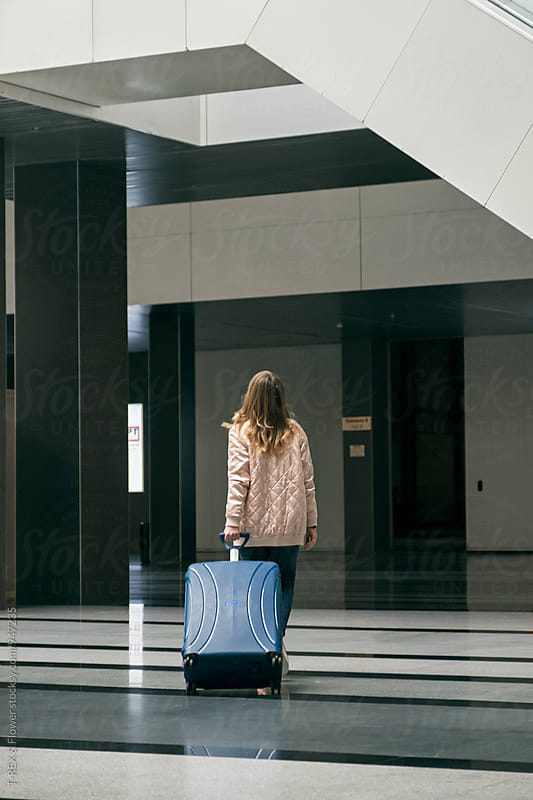 Back view of young woman walking away in airport building by Danil Nevsky for Stocksy United
