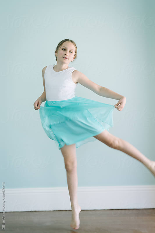 tween girl jumping in a floaty blue dress by Gillian Vann for Stocksy United