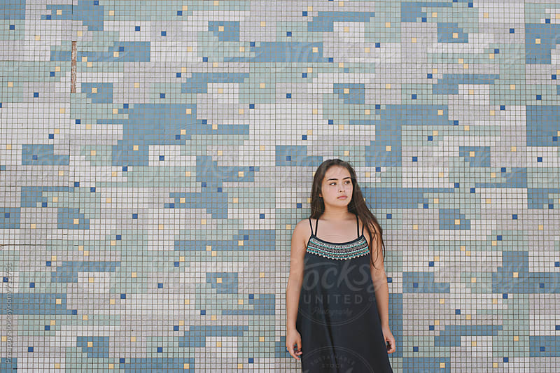 Teenager girl standing against tiled wall by Preappy for Stocksy United