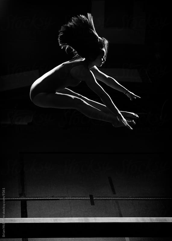 Female gymnast flies high above the beam by Brian McEntire for Stocksy United