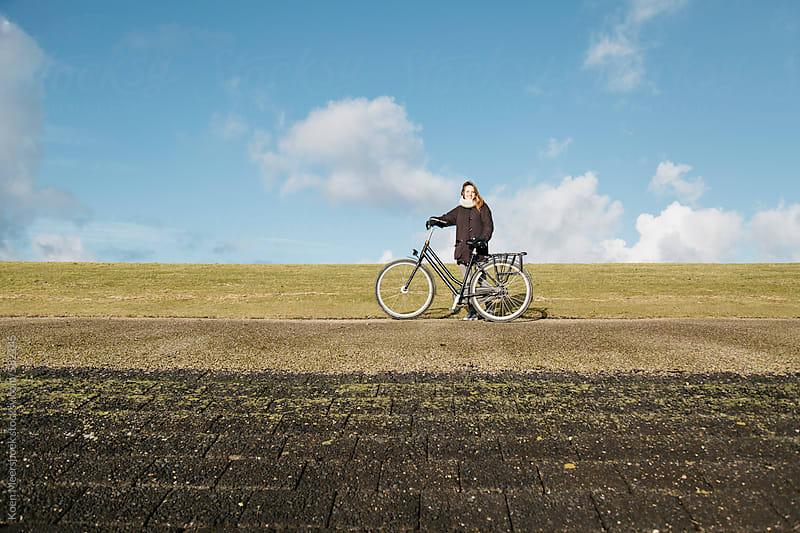 Young having a break to enjoy the sun on a dyke. by Koen Meershoek for Stocksy United