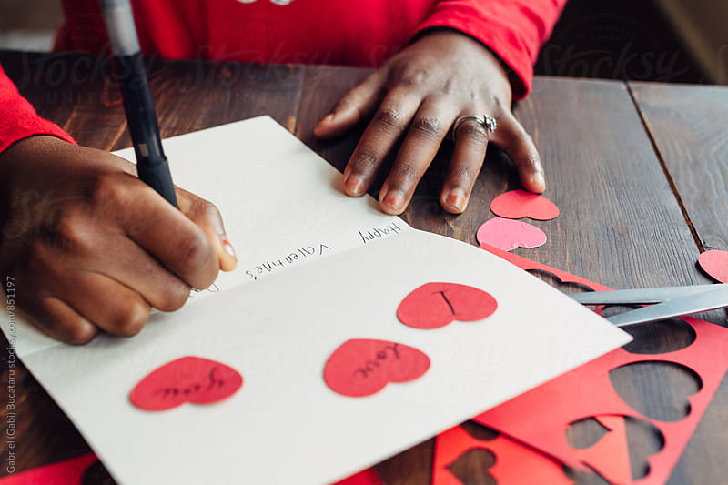 Black girl's hand writing a Valentine's Day card by Gabriel (Gabi) Bucataru for Stocksy United