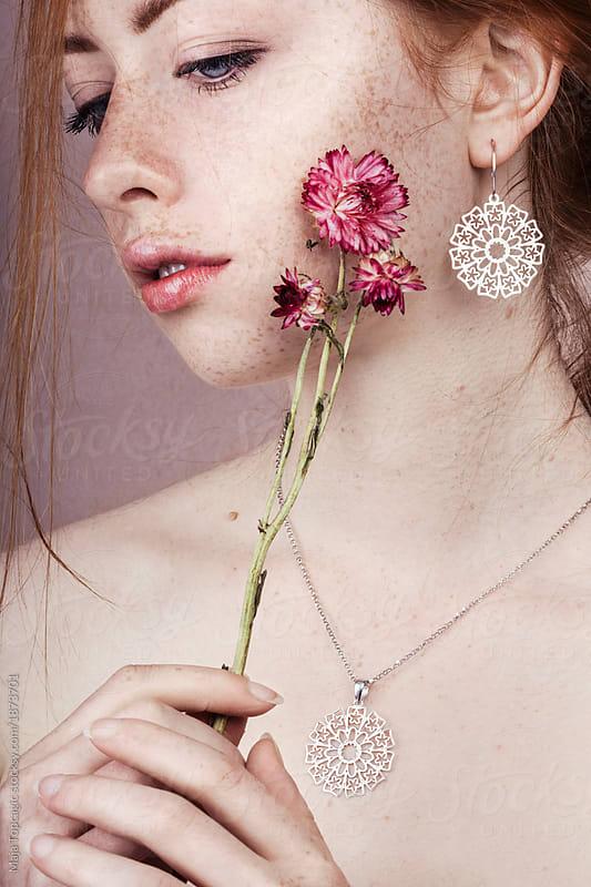 Beautiful redhead holding pink flowers