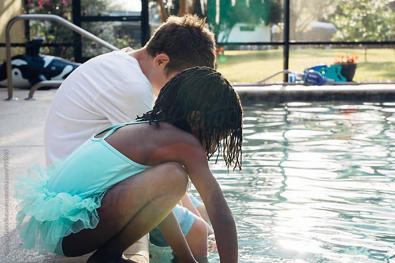 African American girk and caucasian boy by the pool side by Gabriel (Gabi) Bucataru for Stocksy United