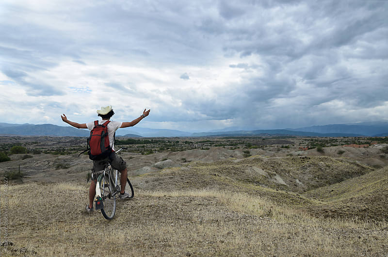 Traveler on a bicycle embracing the sky with his hands up in the prairie  by Alice Nerr for Stocksy United