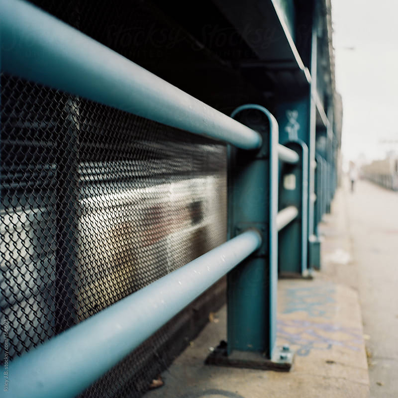 A subway car speeds past a blue bridge railing by Riley J.B. for Stocksy United