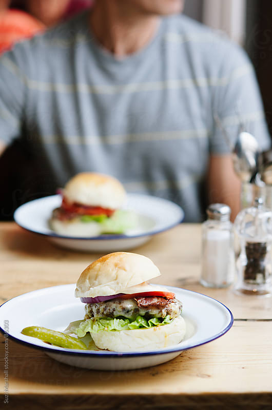 Man sitting at a table with burgers by Suzi Marshall for Stocksy United