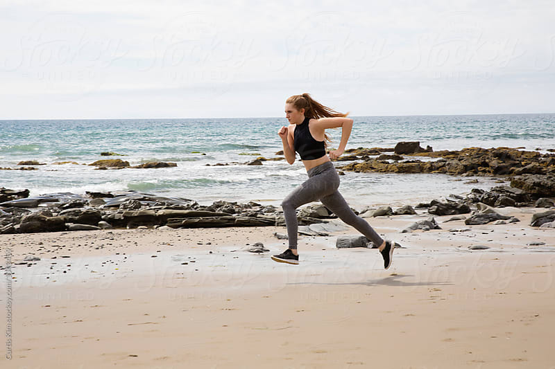 Young woman exercising and running on the beach by Curtis Kim for Stocksy United