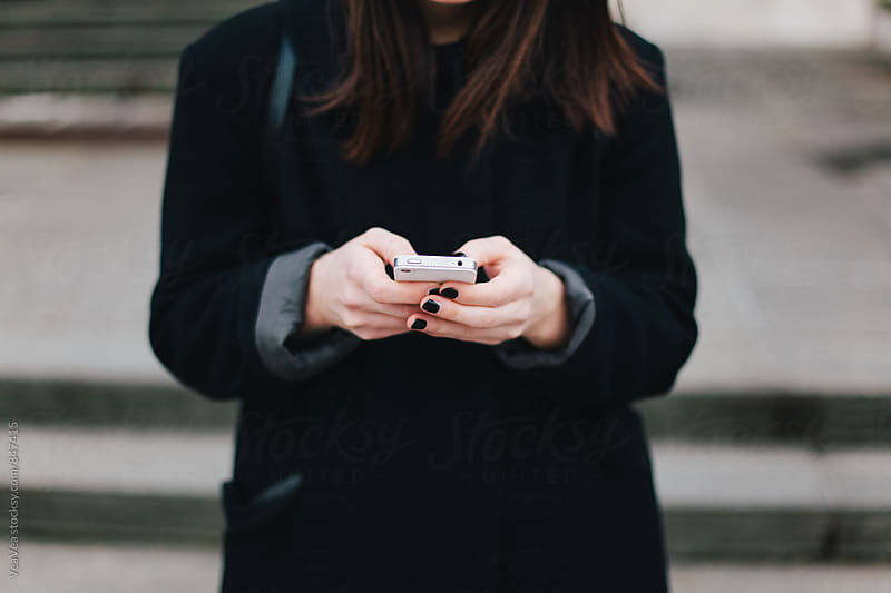Woman in a black coat using her mobile phone in the street by Marija Mandic for Stocksy United