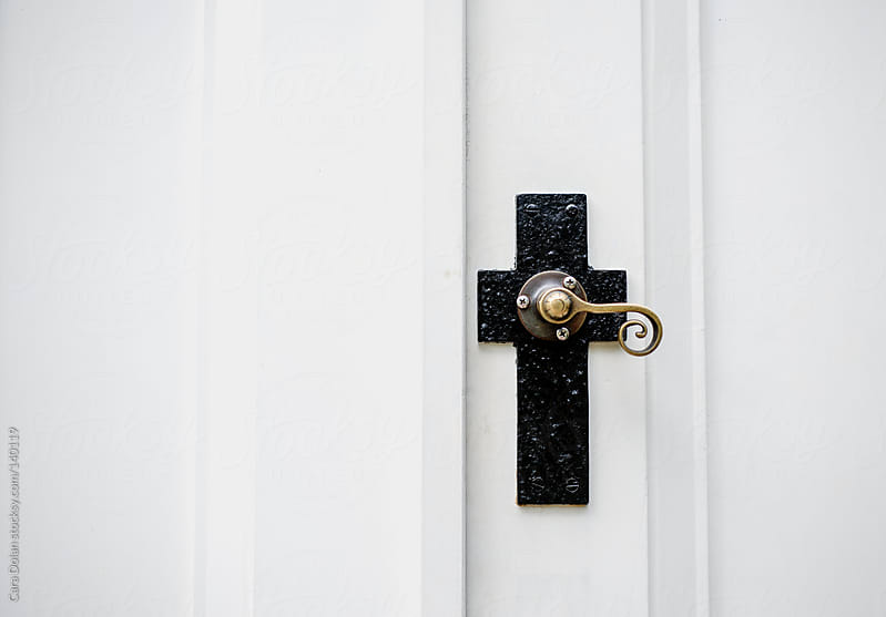 Decorative doorknob of a church is in the shape of a cross  by Cara Dolan for Stocksy United