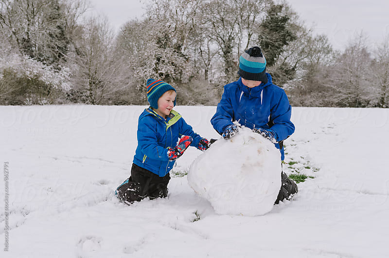 Big brother helps little sibling build a snowman by Rebecca Spencer for Stocksy United