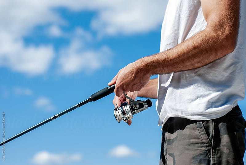 Man holds a fishing pole  by Cara Dolan for Stocksy United