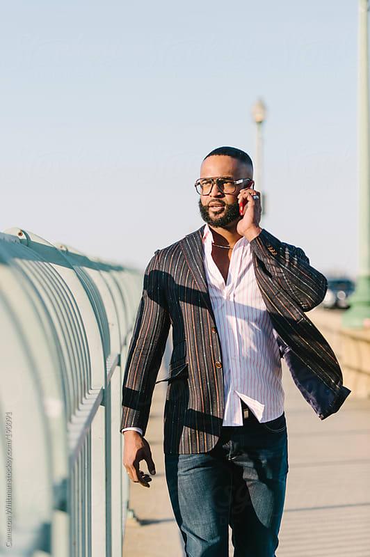 Man talking on phone walking along Key Bridge, Washington DC by Cameron Whitman for Stocksy United