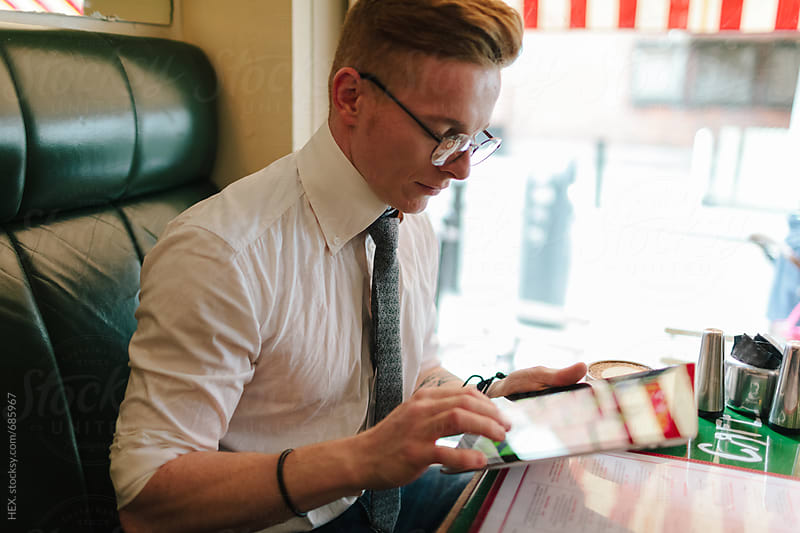 Man using Digital Tablet inside a Coffee Shop by HEX. for Stocksy United