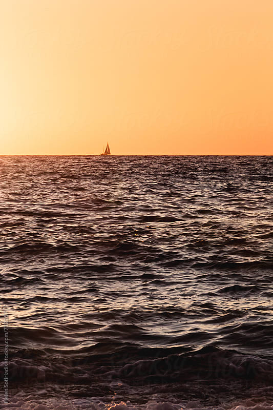 A Small Sailboat on the Horizon Against the Sky at Sunset by Helen Sotiriadis for Stocksy United