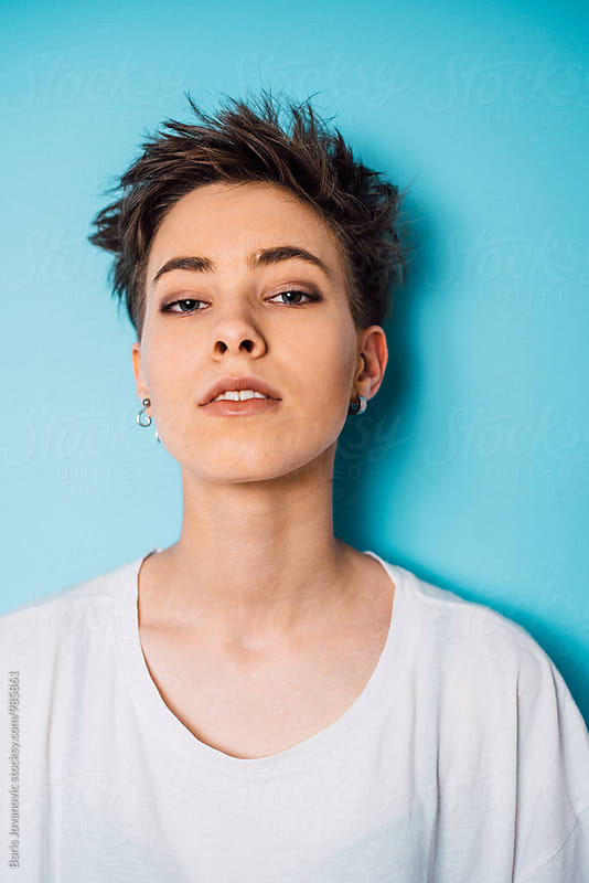 Portrait of beautiful shorthair woman against the blue wall  by Boris Jovanovic for Stocksy United