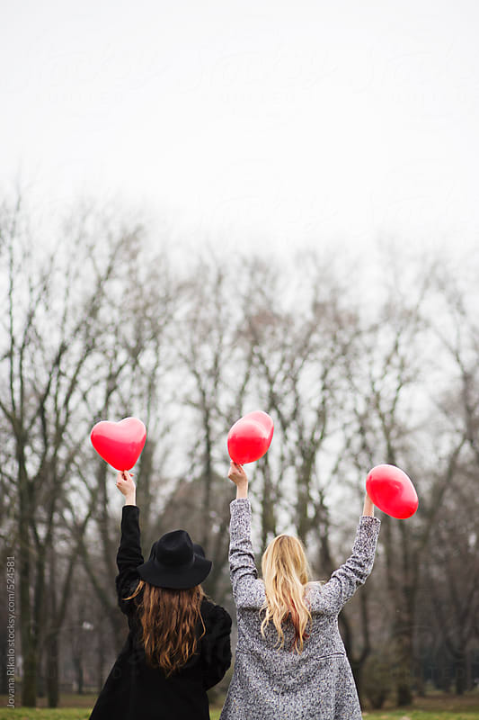Two female friends holding heart shapped balloons for Valentine's day by Jovana Rikalo for Stocksy United