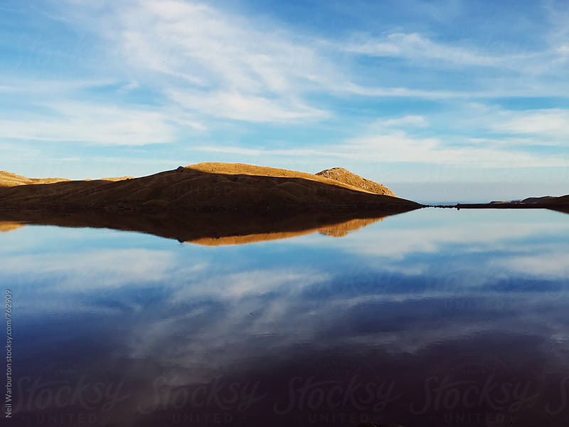Landscape and Sky reflected in mountain lake by Neil Warburton for Stocksy United