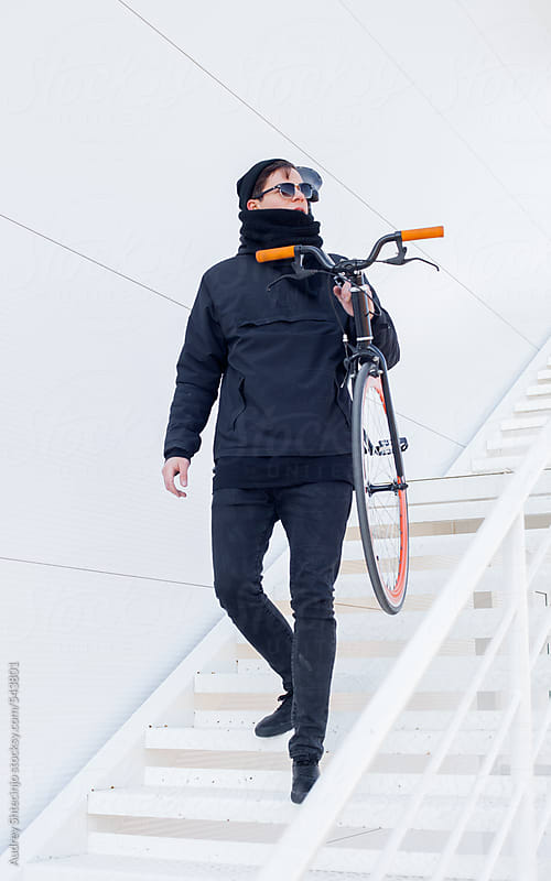 Trendy cyclist in black outfit looking down from white stairs. by Audrey Shtecinjo for Stocksy United