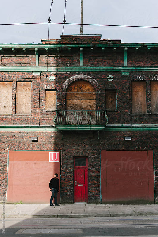Man in the Shadows of Old Brick Building by Briana Morrison for Stocksy United
