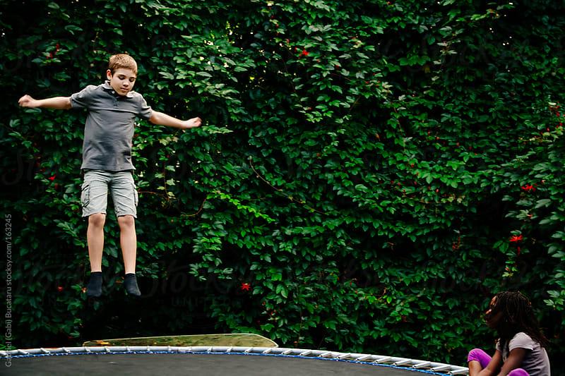 Boy on Trampoline by Gabriel (Gabi) Bucataru for Stocksy United