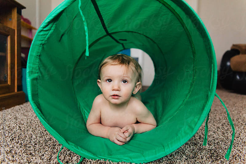 Toddler boy in green tube by Jessica Byrum for Stocksy United