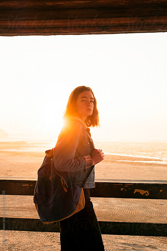 Portrait of brunette backpacker against of sunrise by Danil Nevsky for Stocksy United